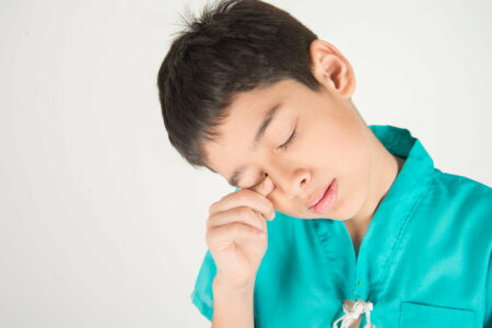 Male child wiping his lower eyelid with finger