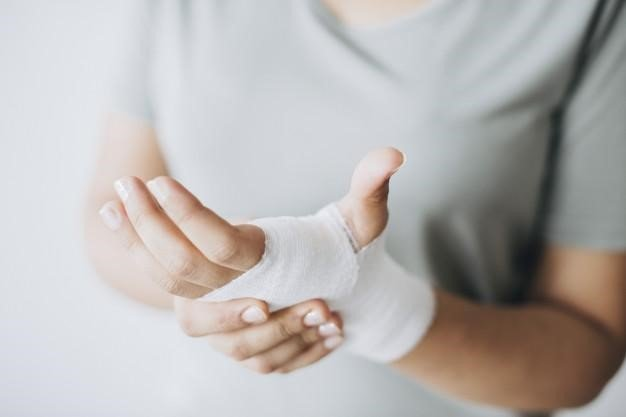 Young woman holding her hand that is wrapped in white medical dressing